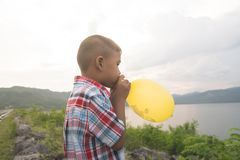 Cute asian little boy blowing balloon stock images