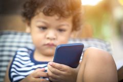 Cute asian little boy is looking smartphone on hand. Cute asian little boy is looking smartphone on hand and sunlight filter effect Royalty Free Stock Images