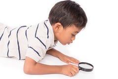 Cute asian little boy play magnifying glass. Asian little boy play magnifying glass Royalty Free Stock Photos