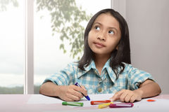 Cute asian little child drawing with colorful crayon. At home royalty free stock image