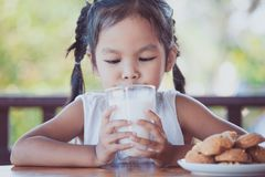 Cute asian little child girl is drinking a milk from glass Royalty Free Stock Image