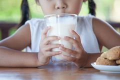 Cute asian little child girl is drinking a milk from glass. With cookies for breakfast royalty free stock photography