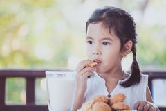 Cute asian little child girl eating cookie with milk. For breakfast with happiness Stock Photos