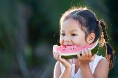 Cute asian little child girl eating watermelon fresh fruit. In the garden Stock Image