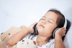 Cute asian little child girl in headphones closed eyes Royalty Free Stock Image