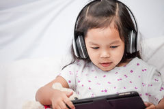 Cute asian little child girl in headphones is using a table Stock Photos