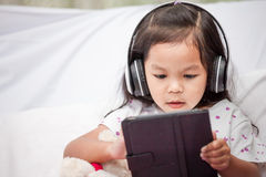 Cute asian little child girl in headphones is using a tablet Stock Photo