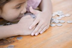 Cute asian little child girl hugging and stingy her money Royalty Free Stock Image