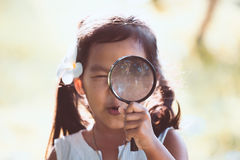 Cute asian little child girl looking through a magnifying glass Stock Photo