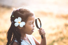 Cute asian little child girl looking through a magnifying glass Stock Images