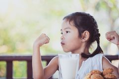 Cute asian little child girl making strong hand while drinking Royalty Free Stock Photo
