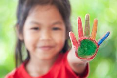 Asian little child girl with painted hands showing fingers number five. Cute asian little child girl with painted hands showing fingers number five stock photo