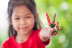 Asian little child girl with painted hands showing fingers number two. Cute asian little child girl with painted hands showing fingers number two stock image
