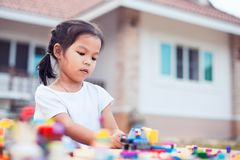 Cute asian little child girl playing with colorful toy blocks Royalty Free Stock Photography