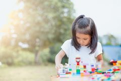 Cute asian little child girl playing with colorful toy blocks Royalty Free Stock Images