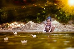 Cute asian little child girl playing paper boat in the riverside. In summer time with fun and happiness Stock Photography
