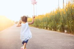 Cute asian little child girl playing with wind turbine. And running on the road in the garden in vintage color tone Stock Photo