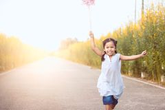 Cute asian little child girl playing with wind turbine. And running on the road in the garden in vintage color tone Stock Photos