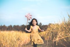 Cute asian little child girl playing with wind turbine. And running in the paddy field in vintage color tone Royalty Free Stock Photography