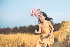 Cute asian little child girl playing with wind turbine. And running in the cornfield in vintage color tone Stock Photo