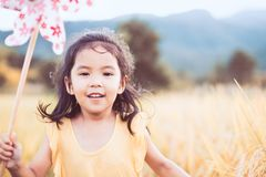 Cute asian little child girl playing with wind turbine. And running in the paddy field in vintage color tone Royalty Free Stock Images