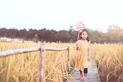 Cute asian little child girl playing with wind turbine. And running in the paddy field in vintage color tone Stock Image