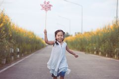 Cute asian little child girl playing with wind turbine. And running on the road in the garden in vintage color tone Royalty Free Stock Image