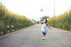 Cute asian little child girl playing with wind turbine and run. Ning on the road in the garden in vintage color tone Royalty Free Stock Photo