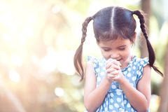 Cute asian little child girl praying with folded her hand Royalty Free Stock Photography