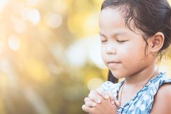 Cute asian little child girl praying with folded her hand Royalty Free Stock Images