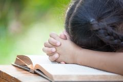 Cute asian little child girl praying with folded her hand Stock Photo