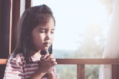 Cute asian little child girl praying with folded her hand. In the room for faith,spirituality and religion concept Royalty Free Stock Images