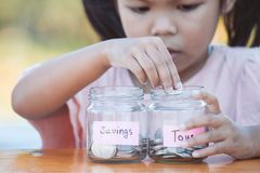 Cute asian little child girl putting coin into glass bottle royalty free stock photos