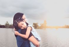 Cute asian little child girl resting on mother`s shoulder royalty free stock images