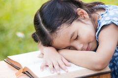 Cute asian little child girl is sleeping and lie down on book. Cute asian little child girl is sleeping and lie down on a book stock photography