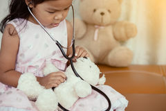 Cute asian little child girl with stethoscope playing doctor Royalty Free Stock Photos