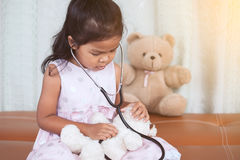 Cute asian little child girl with stethoscope playing doctor Stock Image