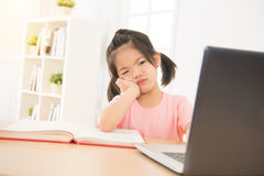 Cute asian little daughter girl looking confused. And hand hold on chin in front of laptop computer at afternoon in the room. kid study concept Stock Image
