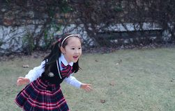 Cute Asian little beautiful girl run in the park royalty free stock photography