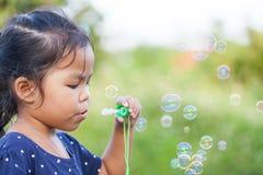 Cute asian little girl is blowing soap bubbles Stock Photo