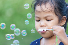 Cute asian little girl is blowing soap bubbles Stock Photos