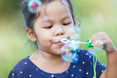 Cute asian little girl is blowing soap bubbles Stock Image