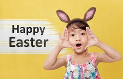 Cute asian little girl with bunny ears celebrate happy easter. Over colored background Stock Photography
