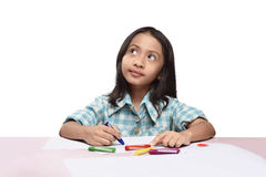 Cute asian little girl with crayon thinking to drawing something Stock Photo