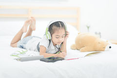 Cute asian little girl doing homework,writing with colourful pen. Cils on bed at home. Elegant design for kid playing, preschool learning and creative art Royalty Free Stock Images