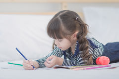 Cute asian little girl doing homework. Writing with colourful pencils on bed at home. Elegant design for kid playing, preschool learning and creative art Stock Photography