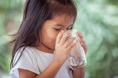 Cute asian little girl drinking fresh water from glass Stock Image