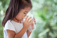 Cute asian little girl drinking fresh water from glass. On green nature background Royalty Free Stock Images