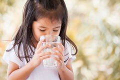 Cute asian little girl drinking fresh water from glass. In vintage color tone Royalty Free Stock Images