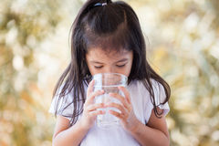 Cute asian little girl drinking fresh water from glass Royalty Free Stock Photography